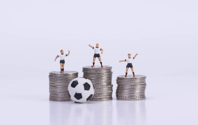 Soccer players standing on coinstacks