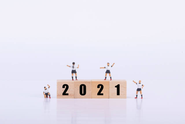 Soccer players standing on wooden cubes with 2021 text