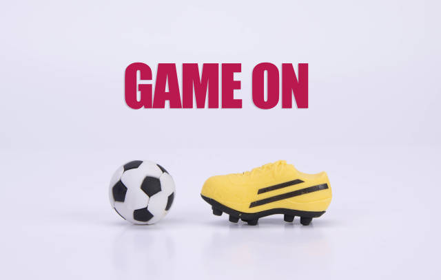 Football shoes and ball with Game on text