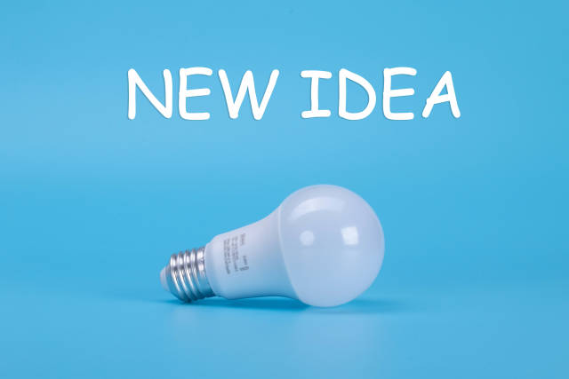 Light bulb with New idea text on blue background