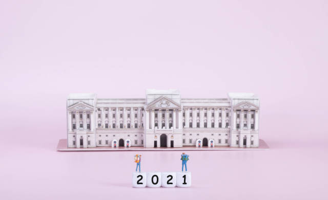 Two travelers standing on blocks with 2021 text in front of Buckingham palace
