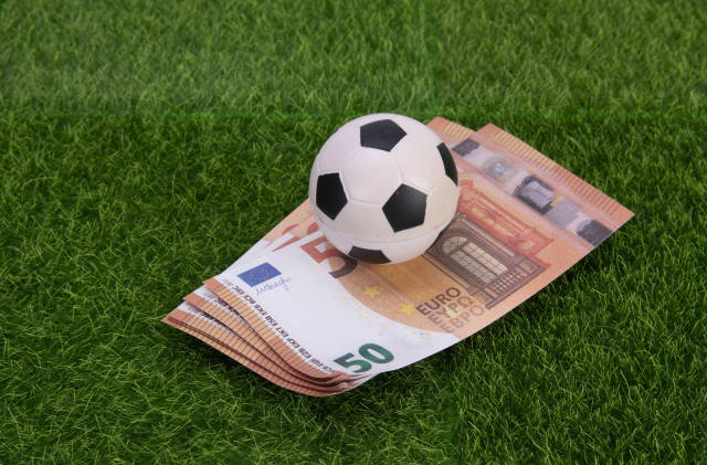 Euro banknotes with soccer ball on grass field
