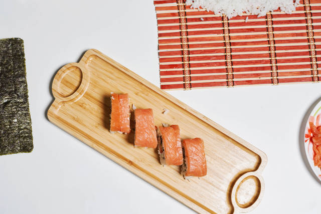 Appetizing sushi rolls on a wooden plate