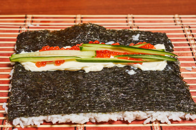Homemade sushi - nori seaweed filled with rice, cucumber slices and red caviar