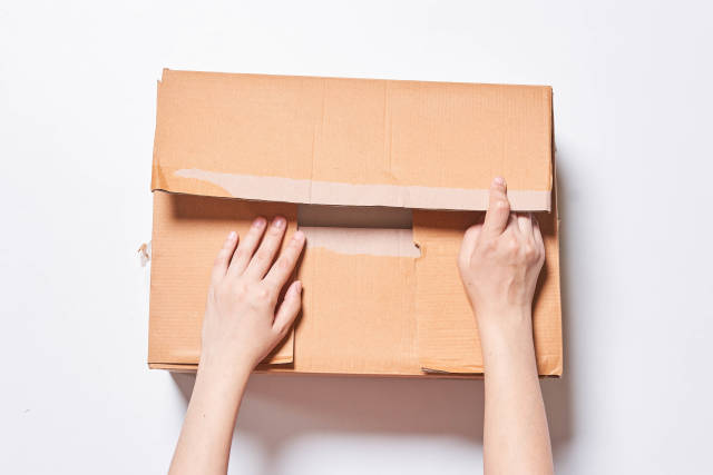 Hands of person open a big box