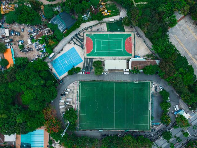 Drohnenaufnahme in der Vogelperspektive von einem Fußballplatz, einem Tennisplatz und einem Basketballplatz mit vielen parkenden Motorrollern in Ho Chi Minh City, Vietnam