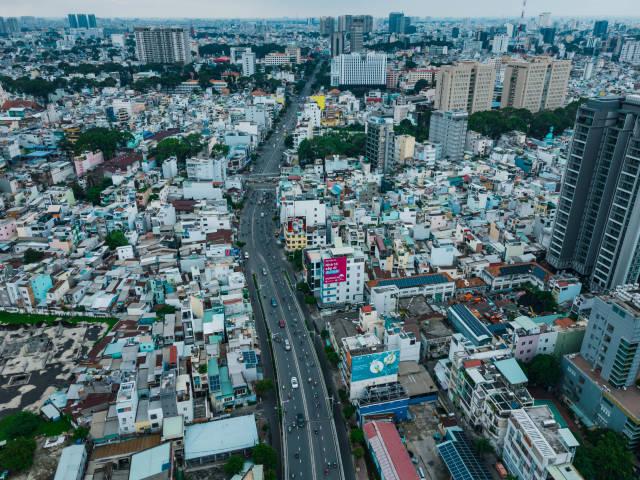 Luftaufnahme von einer Straße mit viel Verkehr, vielen Häusern und Regierungsgebäuden in Distrikt 1 in Ho Chi Minh Stadt, Vietnam