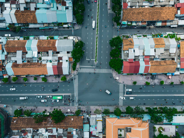 Top View Drone Photo of Traffic at a large Intersection, Buildings, Trees and Alleys in Ho Chi Minh City, Vietnam