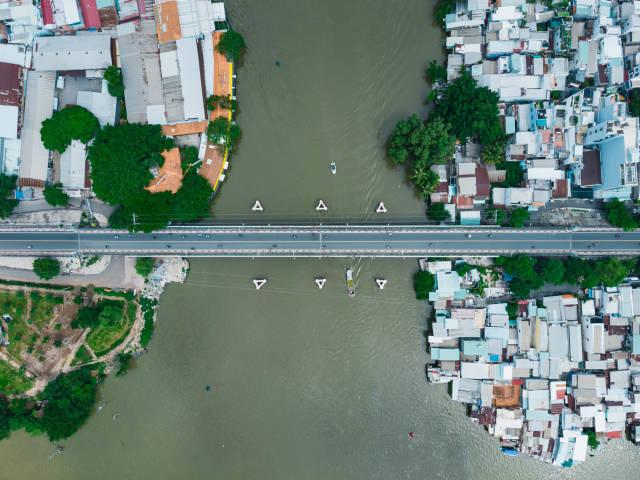 Luftaufnahme einer kleinen Brücke über einen Fluss zwischen zwei Stadtbezirken in Ho Chi Minh Stadt, Vietnam