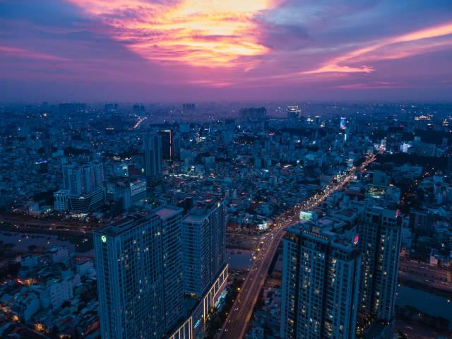 Drohnenaufnahme von Apartmentgebäuden in Distrikt 4 am Saigon Fluss mit Sicht auf das Stadtzentrum bei Sonnenuntergang in Ho Chi Minh Stadt, Vietnam