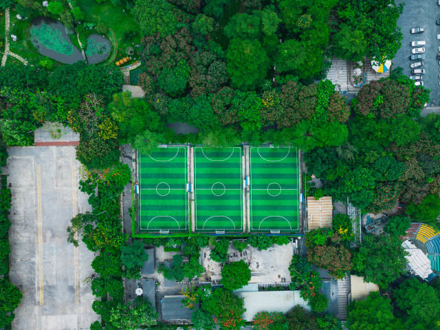 Bird View Drone Photo of three Football Courts within a Public Park with many Trees and a large Parking Space in District 4 in Ho Chi Minh City, Vietnam