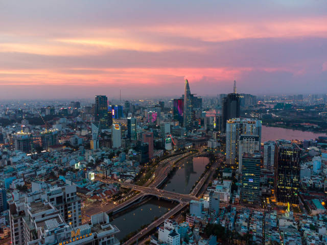 Aerial Drone Photo of District 1 with Reflection of Bitexco Financial Tower in Saigon River at Sunset in Ho Chi Minh City, Vietnam