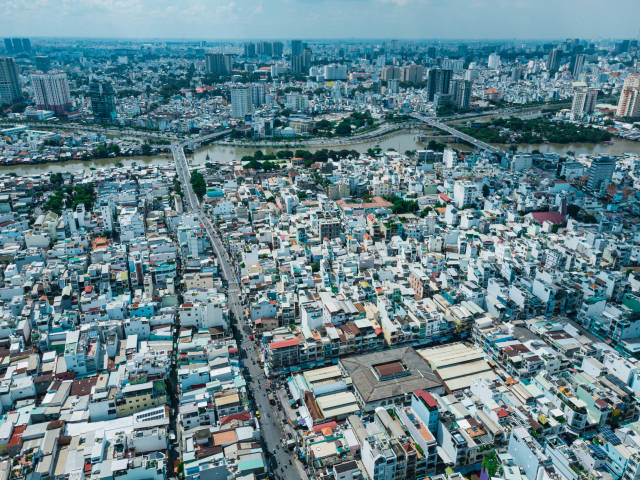 Aerial Drone Shot of many Houses, Schools and Markets along Streets and Bridges over Saigon River in Ho Chi Minh City, Vietnam