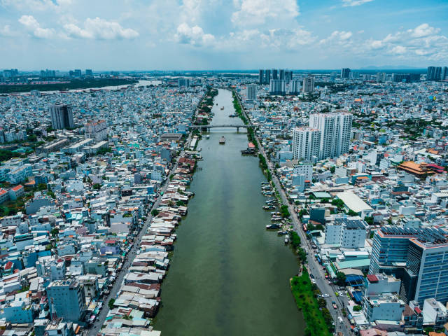 Aerial Drone Photo of Ships on Saigon River along local Houses and Neigborhoods with a View to District 2 in Ho Chi Minh City, Vietnam