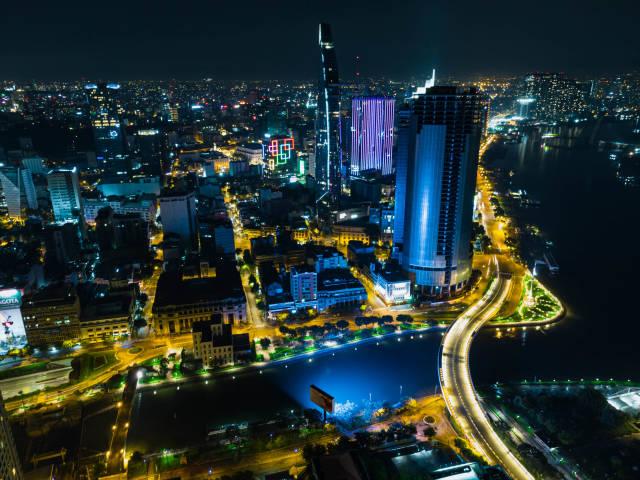 Night Drone Photo of the City Center of Ho Chi Minh City, Vietnam with Bitexco Financial Tower, Saigon One and Saigon River