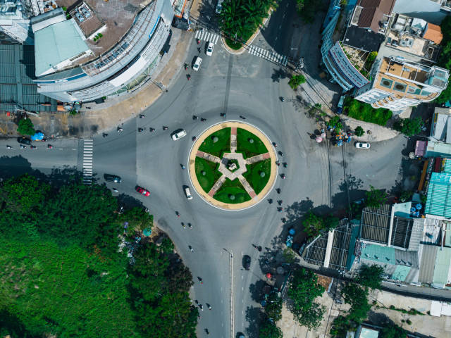 Top View Drone Photo of Cars and Motorbikes going around a Large Roundabout with Monument in District 8 in Ho Chi Minh City, Vietnam