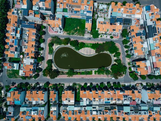 Identische Häuser in der Vogelperspektive mit einem kleinen See und Bäumen in einem Wohngebiet in Distrikt 7 mit einer Drohne fotografiert in Ho Chi Minh Stadt, Vietnam