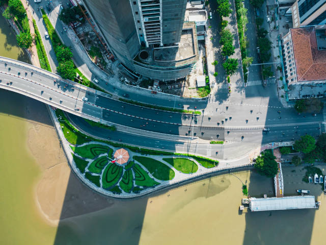 Top View Drone Photo of the historic Thu Ngu Flagpole at Saigon River with Traffic on Khanh Hoi Bridge in Ho Chi Minh City, Vietnam