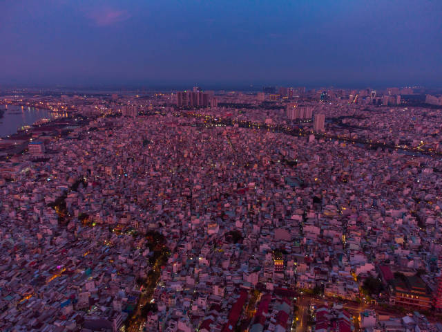 Aerial Drone Photo of many small Houses and Streets in District 4 in the Evening with Khanh Hoi Nha Rong Port at Saigon River in the Background in Ho Chi Minh City, Vietnam