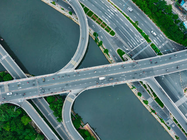 Bird View Drone Photo of Cars, Trucks and Motorbikes crossing a Bridge over Saigon River in Ho Chi Minh City, Vietnam