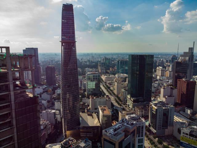 Luftaufnahme der Nguyen Hue Fußgängerzone und Bitexco Financial Tower neben der verlassenen Baustelle vom Saigon One Tower in Ho Chi Minh Stadt, Vietnam