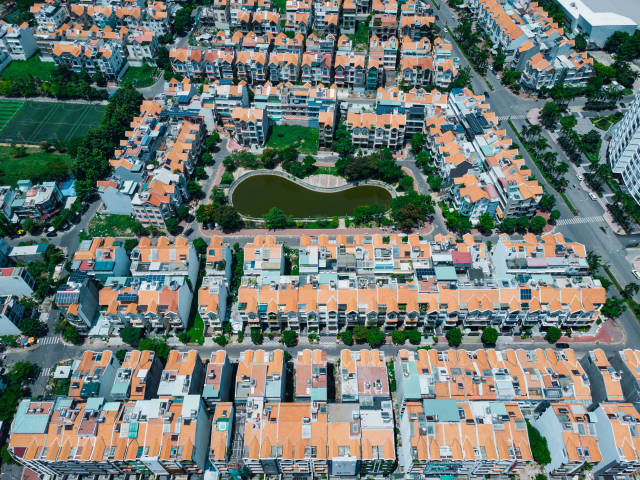 Top View Drone Photo of Identical Houses in a Residential Area with Football Fields and Lake in District 7 in Ho Chi Minh City, Vietnam