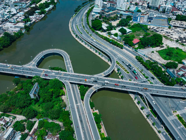 Verkehr mit Motorrollern und Autos auf einer Brücke über Saigon River aus der Luft mit einer Drohne fotografiert in Ho Chi Minh Stadt, Vietnam