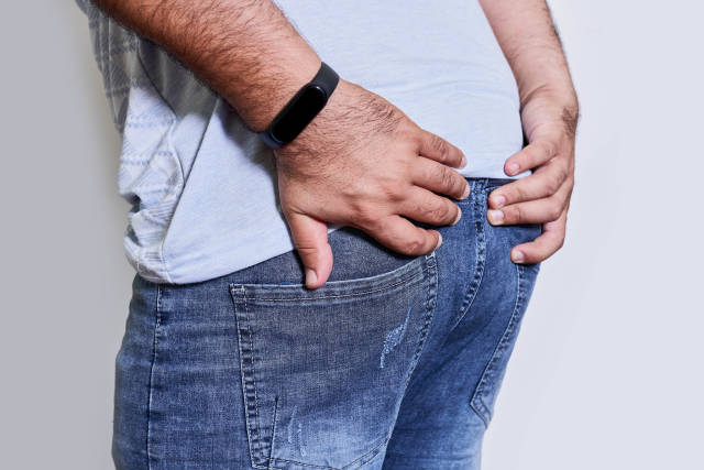 Mans hand holding his bottom because having abdominal pain and hemorrhoids - Health care concept