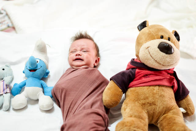Unhappy baby boy lying between plush toys