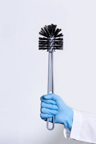 Doctor in medical gloves holds a toilet brush