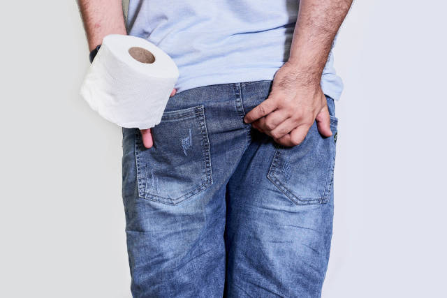 A man suffers from diarrhea and holds toilet paper roll
