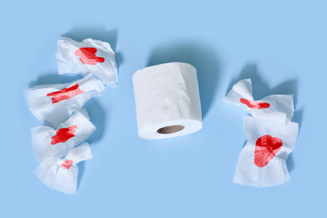 Hemorrhoid problems - sheets of toilet paper with blood on blue background