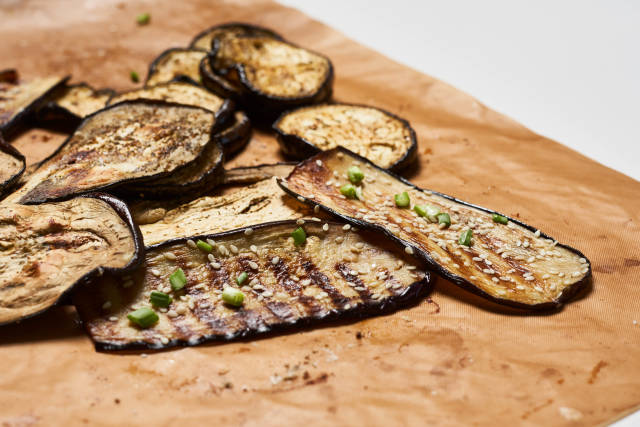 Grilled spicy eggplant slices on a cutting board