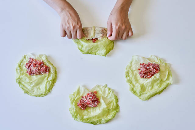 Hands of a woman preparing stuffed cabbage rolls - home cooking concept