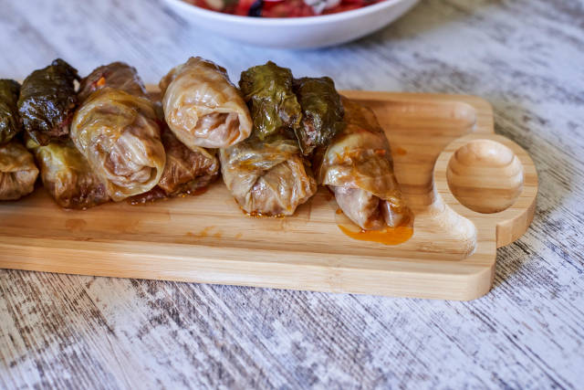 Tasty food - cabbage rolls stuffed with minced meat on a wooden background