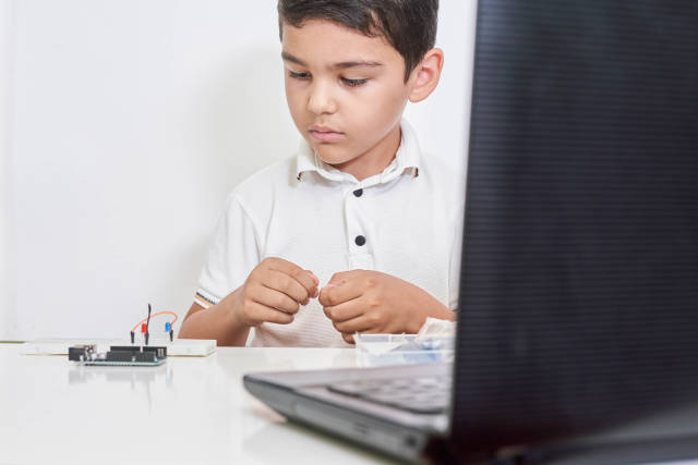 Little boy in robotics school makes robot managed from the constructor
