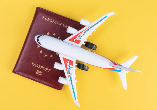 Small airplane on top of the passport with yellow background