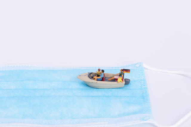 Small boat with German flag on medical face mask