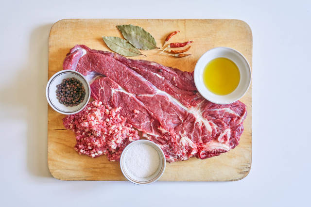 Raw rib-eye steak of beef with herbs and spices on cutting board