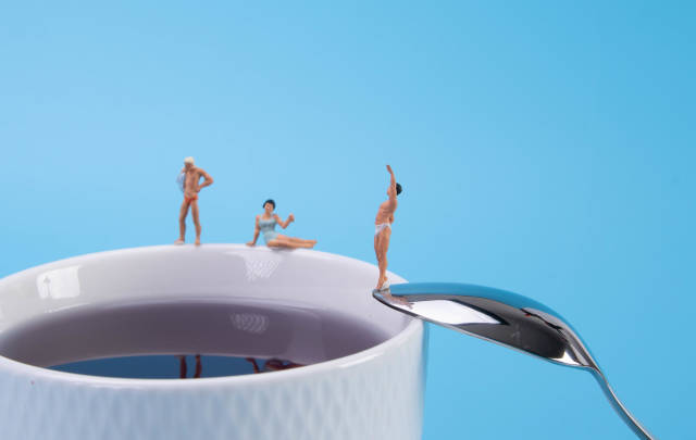 Miniature people relaxing around the coffee cup