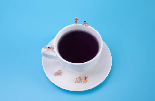 Miniature people relaxing around the coffee cup on blue background
