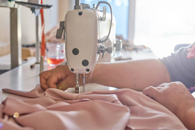 Womans hands sew on a sewing machine