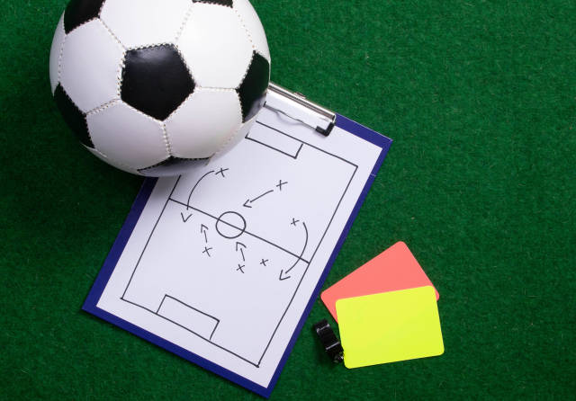 Soccer field tactics on a board with soccer ball and referee cards on green grass
