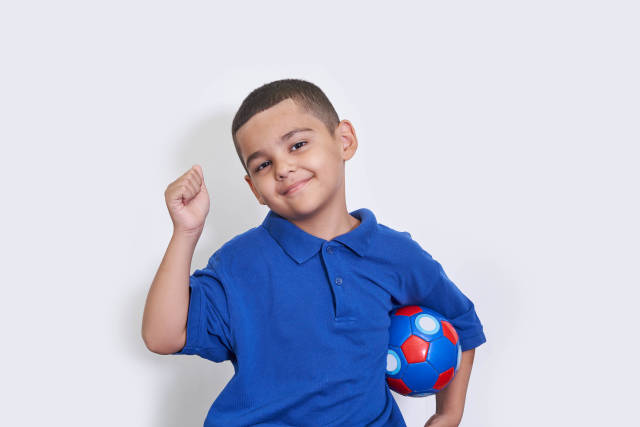Portrait of happy kid boy with soccer ball celebrating championship win