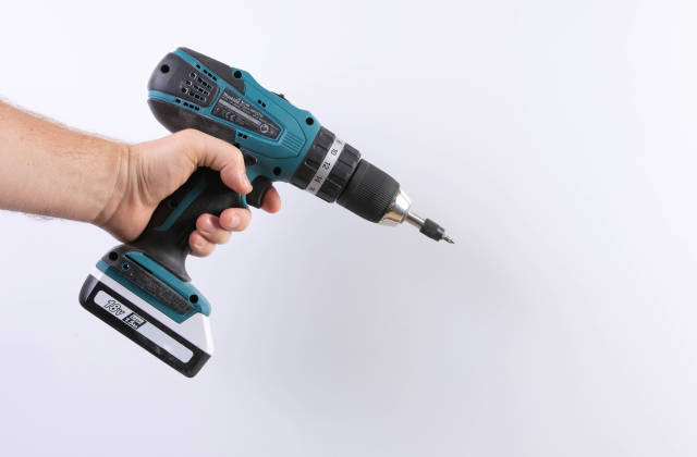 A man holds a cordless drill in his hand on a white background