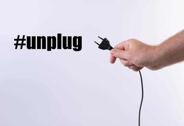 Hand holding black electric European plug isolated on white background with #unplug text