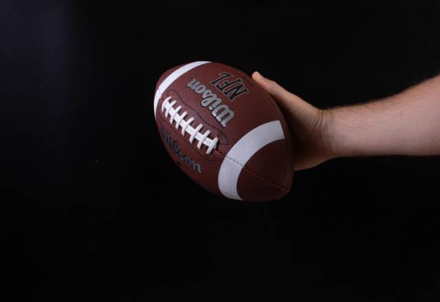Hand holding american football ball