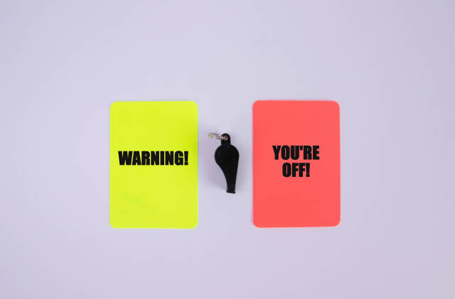 Red and yellow referee cards with Warning and youre off text
