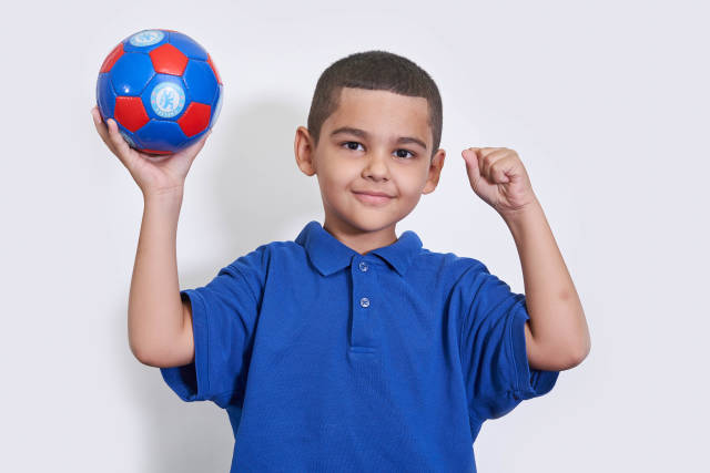 A young boy in blue shirts holding a soccer ball over white background