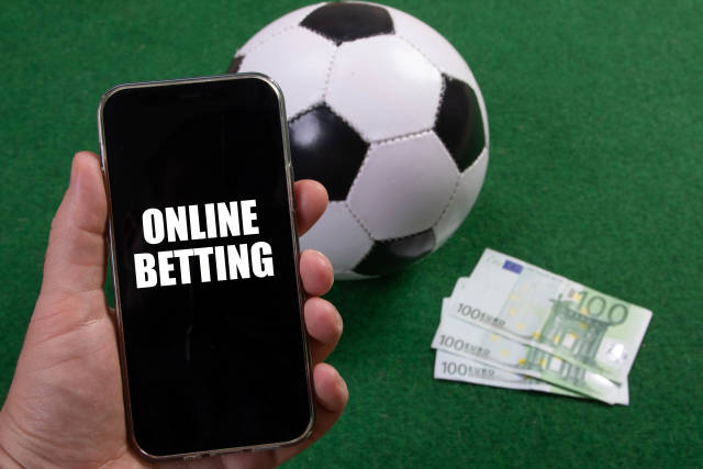 Hand holding smartphone with Online Betting text over a soccer ball and Euro banknotes